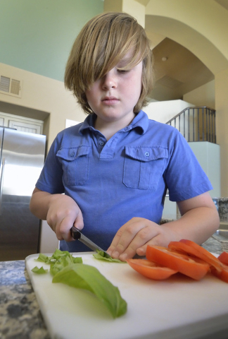 Nine-year-old Jack Newkirk slices some basil and tomatoes at his home in Henderson on Wednesday, June 24, 2015. He is Nevada's winner in Michelle Obama's Healthy Lunchtime Challenge and will atten ...
