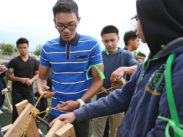 Paolo Velandria, center, and Alvaro Pintado, center right, work with fellow engineering students to build a bridge during a zombie outbreak simulation exercise at Northwest Career & Technical Acad ...