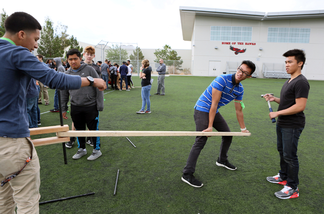 Alvaro Pintado, left, Paolo Velandria, center, and Arnest Reyes, right, work with fellow engineering students to build a bridge during a zombie outbreak simulation exercise at Northwest Career & T ...