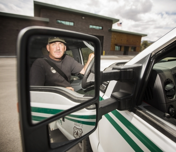 Forest Service prevention patrol officer Ray Johnson's reflection is shown in the side mirror of his vehicle at the Kyle Canyon Fire Station near Spring Mountain Visitor Gateway on July 9. T ...