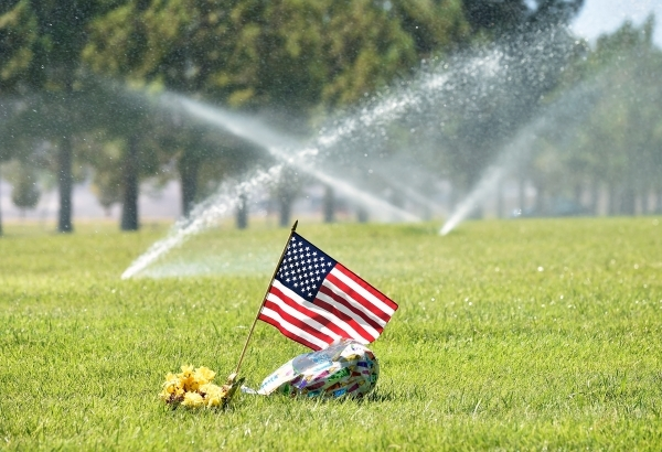 Sprinklers water a recently fertilized area as an American flag flies at a grave site at the Southern Nevada Veterans Memorial Cemetery on Tuesday in Boulder City. A new state law authorizes the s ...