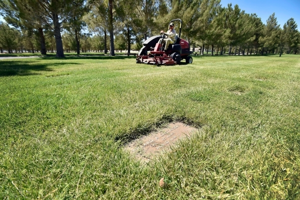 A maintenance worker operates a lawn mower as he trims the grass at the Southern Nevada Veterans Memorial Cemetery on Tuesday in Boulder City. A new state law authorizes the state's two vete ...