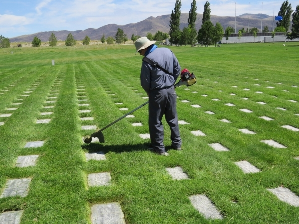 A worker at Northern Nevada Veterans Memorial Cemetery in Fernley edges the grass around grave markers on Tuesday, July 14, 2015. A new state law authorizes Nevada's two veteran cemeteries t ...