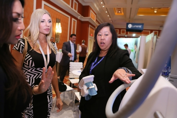 Wendy Suljak, director of marketing at ZELTIQ Aesthetics, from right, speaks to show attendees Amy Biggs and Rita Abreu, both of Honolulu, at the ZELTIQ Aesthetics booth during THE Aesthetic Show. ...