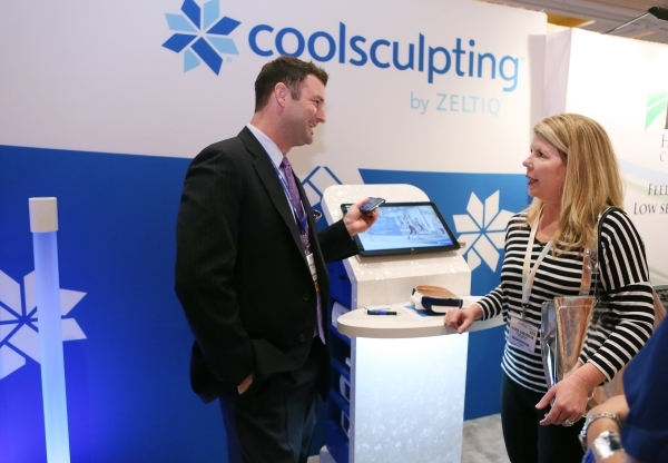 Bryan Steckel, senior area sales manager at ZELTIQ Aesthetics, left, speaks to show attendee Maria Zaborniak, of Ann Arbor, Mich., at the ZELTIQ Aesthetics booth during THE Aesthetic Show at Wynn  ...