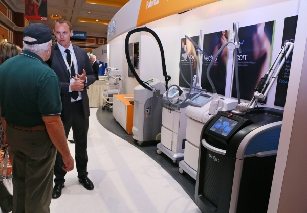 Brad Hallock, right, speaks to attendee Gary Butka, of Brownwood, Texas, at the Cynosure booth during THE Aesthetic Show at Wynn hotel-casino. Aesthetic laser systems can be seen at right. (Ronda  ...