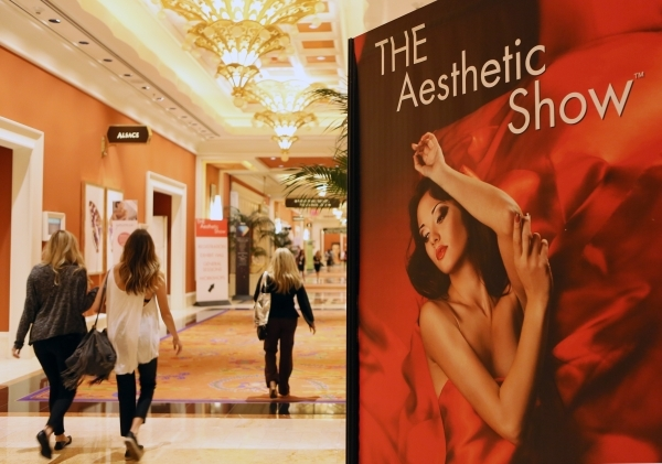 Show attendees walk past a banner for THE Aesthetic Show at Wynn hotel-casino Friday, July 10, 2015, in Las Vegas. (Ronda Churchill/Las Vegas Review-Journal)