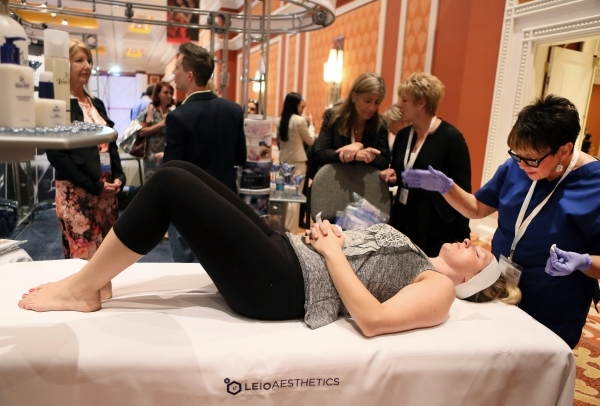 Ellice Turner, front, receives a VisaoMD Brilliance Peel by Valerie Zehler, right, a medical esthetician, during The Aesthetic Show on July 10 at Wynn hotel-casino. (Ronda Churchill/Las Vegas Revi ...