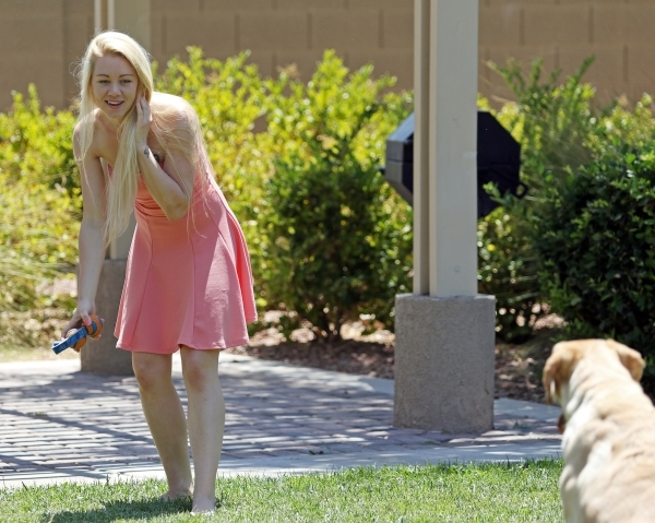 Alexis Gibson plays fetch with her dog Bubba in a grassy area near her home in North Las Vegas. Gibson, who was born with HIV, recently graduated from the University of Phoenix and is an advocate  ...
