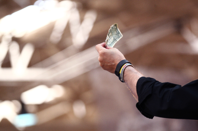 Wisconsin Gov. Scott Walker, a Republican presidential candidate, holds up a dollar bill while speaking during a campaign stop at Harley-Davidson, 2260 S. Rainbow Blvd., in Las Vegas on Tuesday, J ...