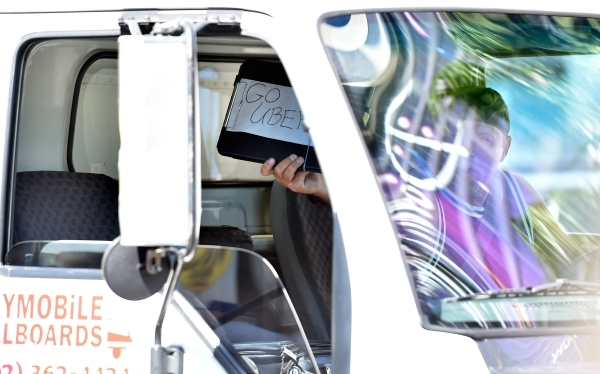 A driver of a mobile billboard displays his approval for the Uber service as he drives along the Strip on May 29. Several dozen cabdrivers walked in protest in front of Caesars Palace in oppositio ...