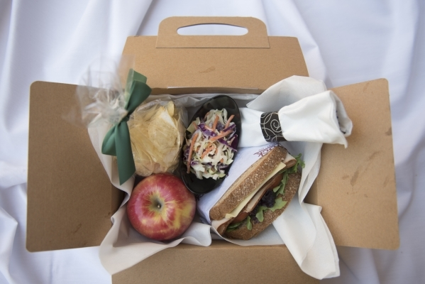 A premium picnic box lunch from Red Rock Resort features a turkey and Swiss sandwich, chips, coleslaw and an apple.  Jason Ogulnik/Las Vegas Review-Journal