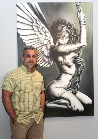 """Artist Adolfo Gonzalez and his acrylic painting """"Enslaved Angel,"""" which is on display through Oct. 3 at Left of Center Gallery as part of the """"Thicker Than Blood"""" exhibit, whic ..."""