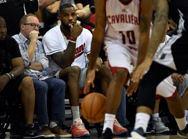 Cleveland Cavaliers general manager David Griffin, left, and player LeBron James watch the Cavaliers play the Minnesota Timberwolves during an NBA Summer League  game at the Cox Pavilion on Friday ...
