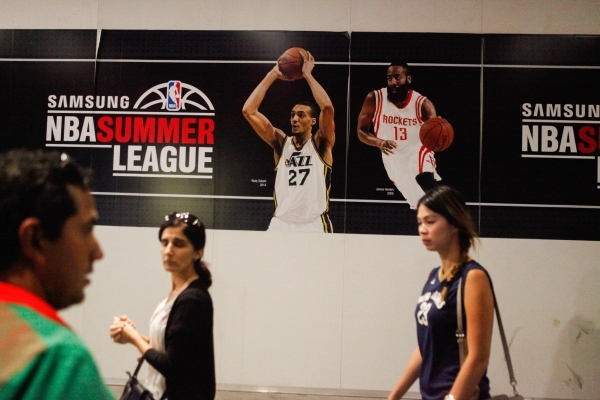 People walk by a mural featuring famous players that participated in the NBA Summer League at the Thomas and Mack Center in Las Vegas on Sunday, July 19, 2015. (James Tensuan/Las Vegas Review-Jour ...