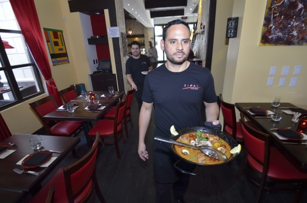 Food runner Francisco Flores takes an order of paella to a table at Tapas by Alex Stratta. (Bill Hughes/Las Vegas Review-Journal)
