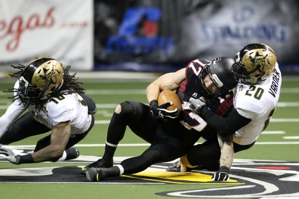 Tanner Varner of the Las Vegas Outlaws tackles Collin Taylor of the Cleveland Gladiators on Sunday, June 7, 2015, in Las Vegas. The Outlaws lost to the Gladiators 63 to 44. (James Tensuan/Las Vega ...