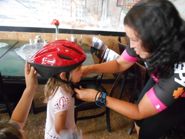 Gianna Meccariello, 5, is fitted for a helmet by Tina Lucero of the Velo Vegas/Every Kid a Bike cycling team at Villa Pizza on 3385 S. Durango Road in Las Vegas on Saturday, July 18, 2015. The Sou ...