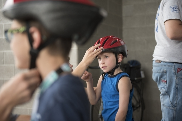 Six-year-old Matthew Freedman, center, gets fitted for a bicycle helmet at a giveaway event Saturday at Black Mountain Recreation Center in Henderson. Jason Ogulnik/Las Vegas Review-Journal