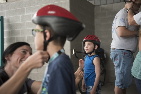 Shannon Gaffney fits a helmet on David Freedman, 6, as Matthew Freedman, 6, looks on at the bicycle helmet giveaway at Black Mountain Recreation Center in Henderson, Saturday, July 18, 2015. (Jaso ...