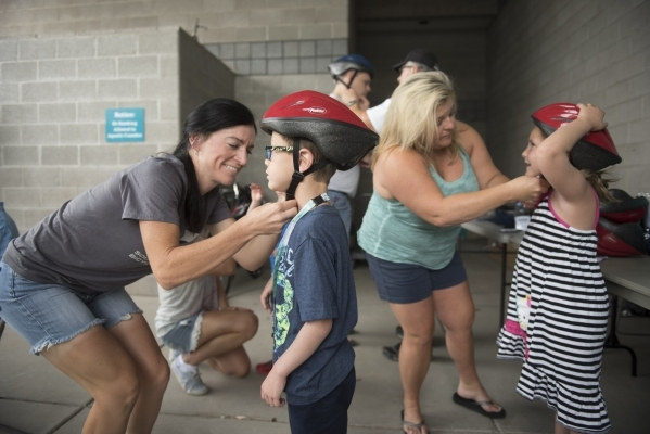 Shannon Gaffney, from left, fits a helmet on Matthew Freedman, 6, as Linda Floth fits a helmet for Madison Freedman, 6, gets fitted for a helmet at the bicycle helmet giveaway at Black Mountain Re ...
