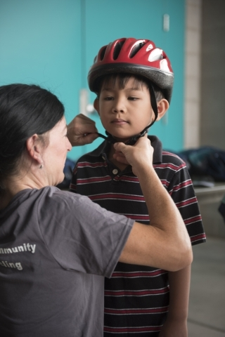 Shannon Gaffney fits Adriel Tabilog, 6, with a helmet at the bicycle helmet giveaway at Black Mountain Recreation Center in Henderson, Saturday, July 18, 2015. (Jason Ogulnik/Las Vegas Review-Journal)