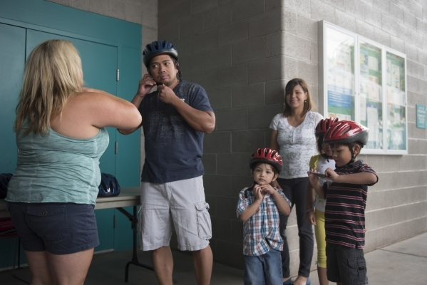 Linda Floth, left, fits members of the Tabilog family, from left, Alexander, Alec, 3, Gina, Guilia, 7, and Adriel, 6, for helmets at an event Saturday at Black Mountain Recreation Center in Hender ...