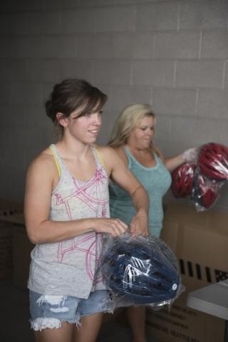 Lisa Leonard, left, and Linda Floth prepare helmets to be donated at the bicycle helmet giveaway at Black Mountain Recreation Center in Henderson, Saturday, July 18, 2015. (Jason Ogulnik/Las Vegas ...