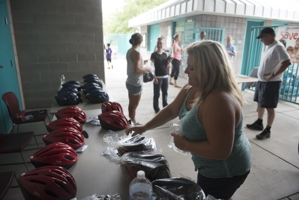 Linda Floth prepares helmets to be donated at the bicycle helmet giveaway at Black Mountain Recreation Center in Henderson, Saturday, July 18, 2015. (Jason Ogulnik/Las Vegas Review-Journal)
