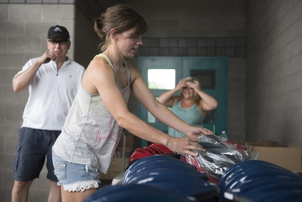 Don Bauer, from left, Lisa Leonard and Linda Floth prepare helmets to be donated at the bicycle helmet giveaway at Black Mountain Recreation Center in Henderson, Saturday, July 18, 2015. (Jason Og ...