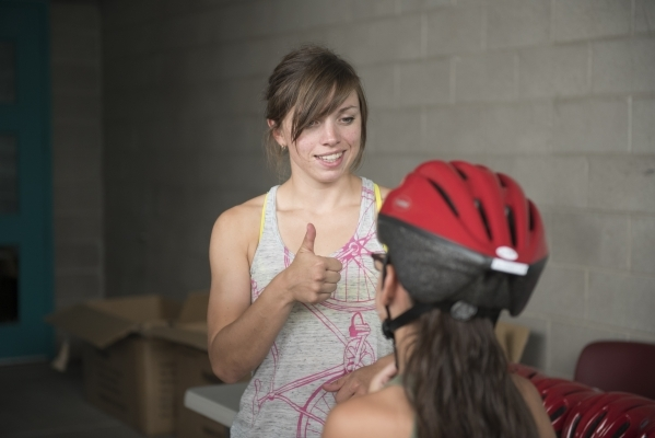 Lisa Leonard gives a thumbs up to indicate a helmet that fits well at the bicycle helmet giveaway at Black Mountain Recreation Center in Henderson, Saturday, July 18, 2015. (Jason Ogulnik/Las Vega ...