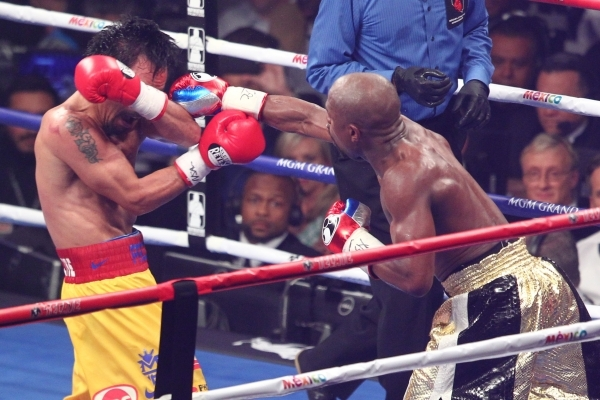 Floyd Mayweather Jr., right, connects with Manny Pacquiao in their welterweight unification boxing match at the MGM Grand Garden Arena in Las Vegas on Saturday, May 2, 2015. (Chase Stevens/Las Veg ...