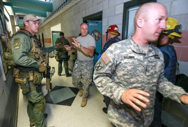 Carson City Sheriff's SWAT members evacuate offices during an active shooter drill at the Adjutant General complex in Carson City, Nev., on Wednesday, July 22, 2015. Nevada National Guard, C ...