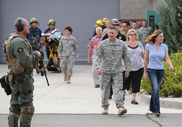 Workers are evacuated during an active shooter drill at the Adjutant General complex in Carson City, Nev., on Wednesday, July 22, 2015. Nevada National Guard, Carson City Sheriff and Fire departme ...