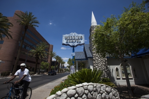 A bicyclist passes by Graceland Wedding Chapel, 619 S. Las Vegas Blvd., on Tuesday, July 21, 2015, in downtown Las Vegas. Clark County commissioners on Tuesday approved raising the marriage licens ...