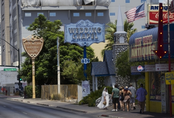 A wedding party walks along Las Vegas Boulevard near Garces Avenue on Tuesday, July 21, 2015, in downtown Las Vegas. Clark County commissioners on Tuesday approved raising the marriage license fee ...
