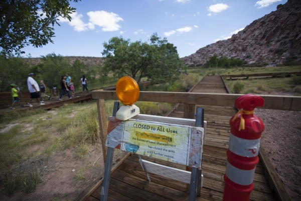 A blocked off portion of the boardwalk is seen as people walk by at the Red Springs picnic area in the Red Rock Canyon National Conservation Area on Tuesday, July 21, 2015. A portion of the boardw ...