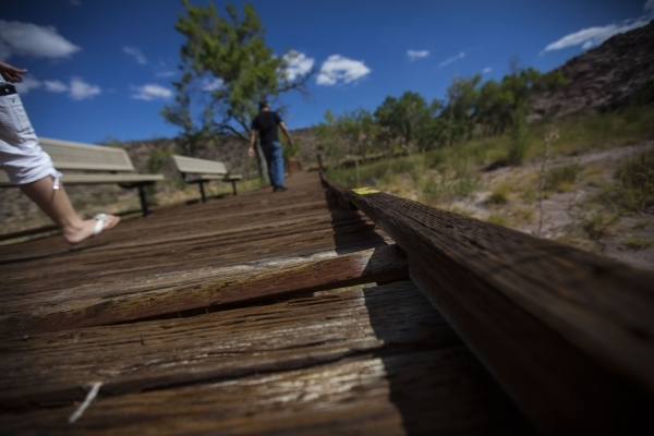 Part of a wooden plank sticks up from the boardwalk as people walk by at the Red Springs picnic area in the Red Rock Canyon National Conservation Area on Tuesday, July 21, 2015. A portion of the b ...