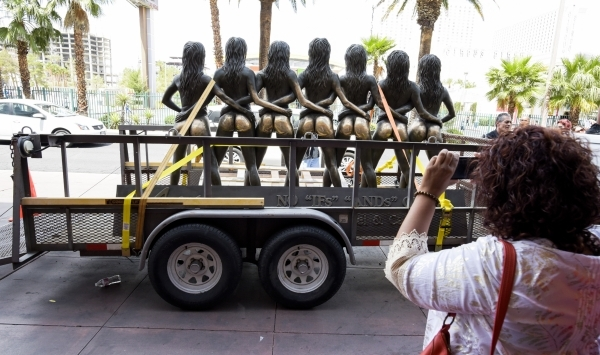 "A visitor photographs the ""Crazy Girls"" statue loaded on a trailer outside the Riviera in May, when the iconic hotel-casino closed. The statue will be moved Monday to its new home at Pla ..."