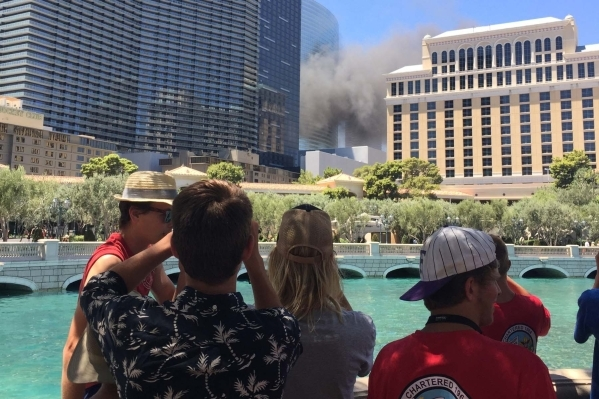 Tourists near the Bellagio watch as smoke rises near the Cosmopolitan hotel-casino on the Strip in Las Vegas on Saturday, July 25, 2015. (Joshua Dahl/Las Vegas Review-Journal)