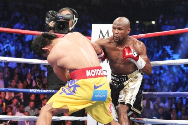 Floyd Mayweather Jr. hits Manny Pacquiao with a right hand during their welterweight title unification fight at the MGM Grand Garden on May 2. Mayweather won by unanimous decision. Mayweather is e ...