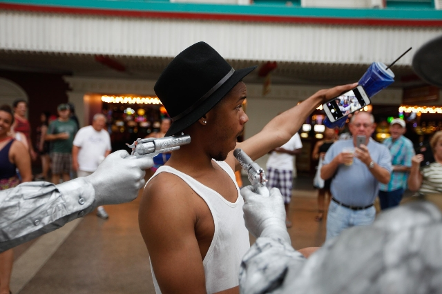 Chris Johnsun takes a selfie with the Silver and Gold Statues on Fremont Street on Wednesday, July 29 2015. The city hopes to set up zones for street performers on Fremont Street.