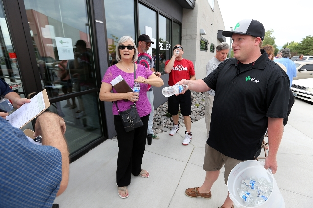 Manager Garrett Newman passes out water bottles to people waiting for the opening of Silver State Relief in Sparks on Friday, July 31, 2015. More than 50 people with state-authorized medical cards ...