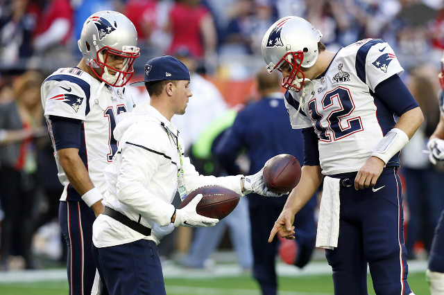 Feb 1, 2015; Glendale, AZ, USA; New England Patriots quarterback Tom Brady (12) looks at footballs before the game against the Seattle Seahawks in Super Bowl XLIX at University of Phoenix Stadium. ...