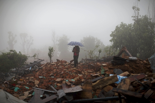 A local villager holds an umbrella as he walks amid debris at a devastated area following Saturday's earthquake, at Paslang village in Gorkha, Nepal April 28, 2015. (REUTERS/Athit Perawongmetha)