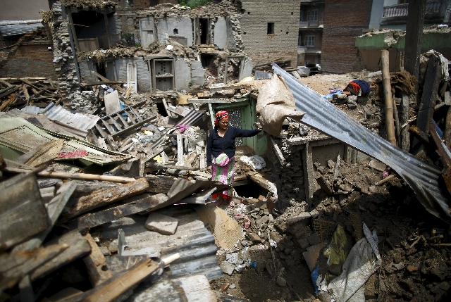 A woman stands on the debris of collapsed houses after a fresh 7.3-magnitude earthquake struck Nepal, in Sankhu May 12, 2015. (Navesh Chitraker/Reuters)