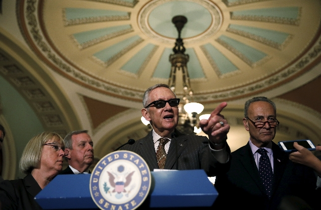Senate Minority Leader Harry Reid, D-Nev., center, listens to questions from the media after their party's caucus luncheons on Capitol Hill in Washington, D.C., June 23, 2015. (Reuters/Gary  ...