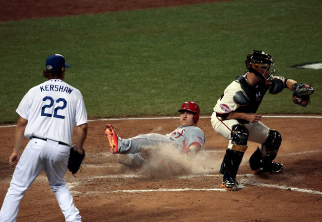 American League outfielder Mike Trout (27) of the Los Angeles Angels slides home to score against National League catcher Buster Posey (28) of the San Francisco Giants as National League pitcher C ...