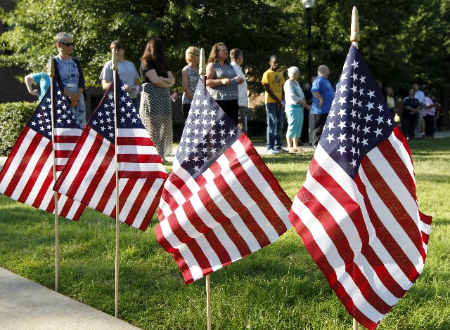 Four flags, representing four Marines killed in an attack by a gunman, are seen at the entrance to the University of Tennessee in Chattanooga college during a vigil in Chattanooga, Tennessee July  ...