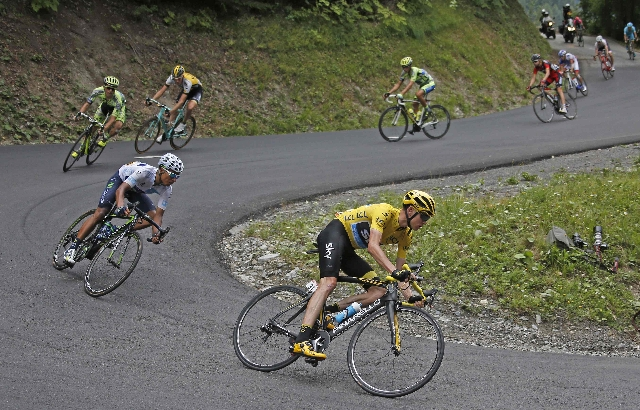 From R-L, Team Sky rider Chris Froome of Britain, the race overall leader's yellow jersey, speeds downhill followed by Movistar rider Nairo Quintana of Colombia and Tinkoff-Saxo rider Albert ...